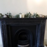 Simple mantelpieces with candles and eucalyptus